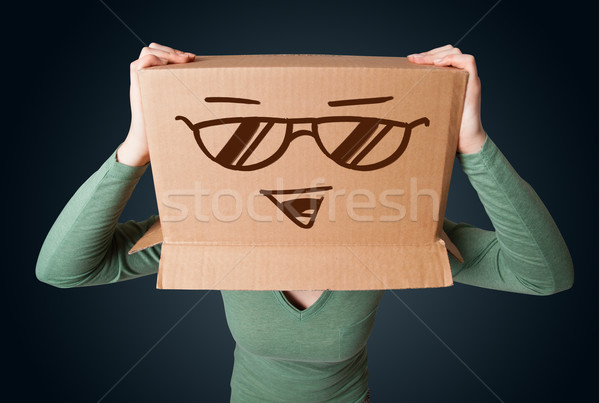 Young lady gesturing with a cardboard box on her head with smile Stock photo © ra2studio