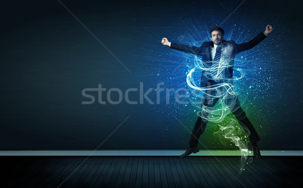 Talented cheerful businessman jumping with glowing energy lines Stock photo © ra2studio