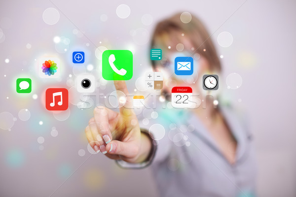 Young businesswoman pressing colorful mobile app icons with boke Stock photo © ra2studio