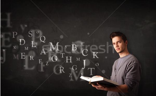 молодым человеком чтение книга алфавит письма из Сток-фото © ra2studio