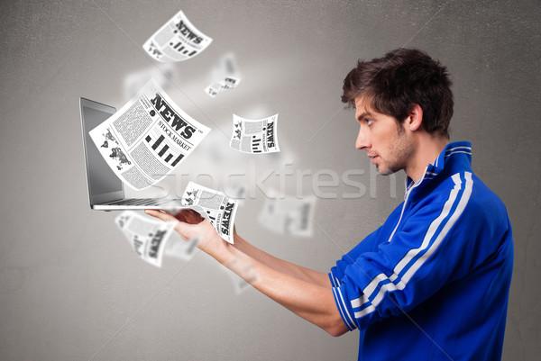 Młody człowiek laptop czytania wybuchowy wiadomości Zdjęcia stock © ra2studio