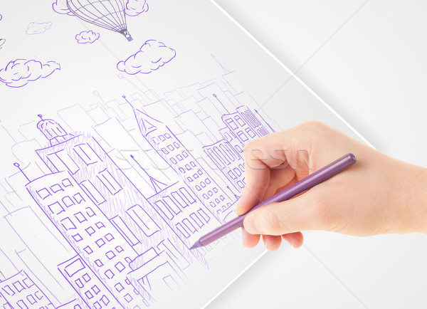 A person drawing sketch of a city with balloons and clouds on a plain paper Stock photo © ra2studio