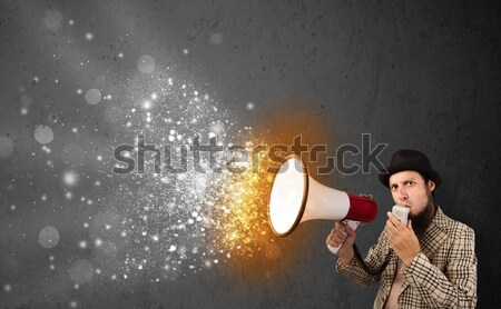 Guy shouting into megaphone and glowing energy particles explode Stock photo © ra2studio