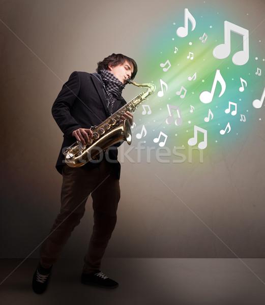 Młodych muzyk gry saksofon muzyki zauważa atrakcyjny Zdjęcia stock © ra2studio