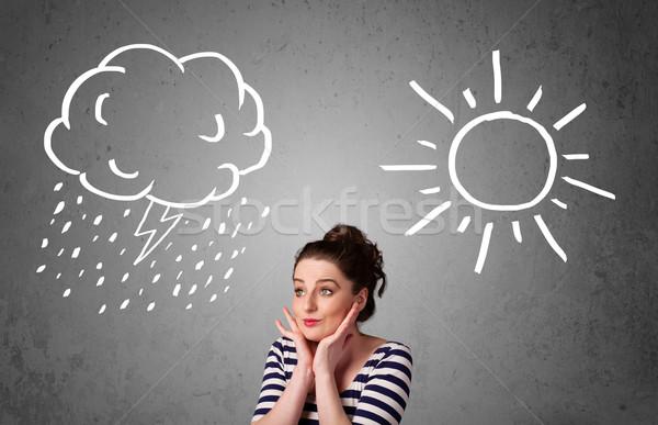 Woman standing between a sun and a rain drawing Stock photo © ra2studio