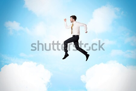 Business person jumping over clouds in the sky Stock photo © ra2studio