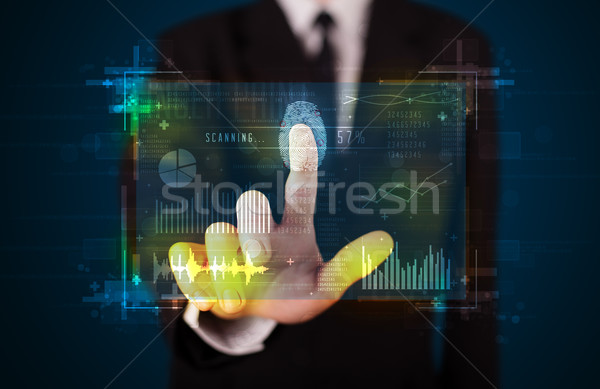 Young businessman pressing modern technology panel with finger p Stock photo © ra2studio