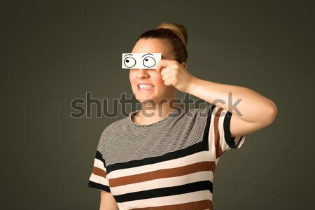 Young silly girl looking with hand drawn eye balls on paper Stock photo © ra2studio