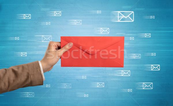 Hand holding envelope with message symbols around Stock photo © ra2studio