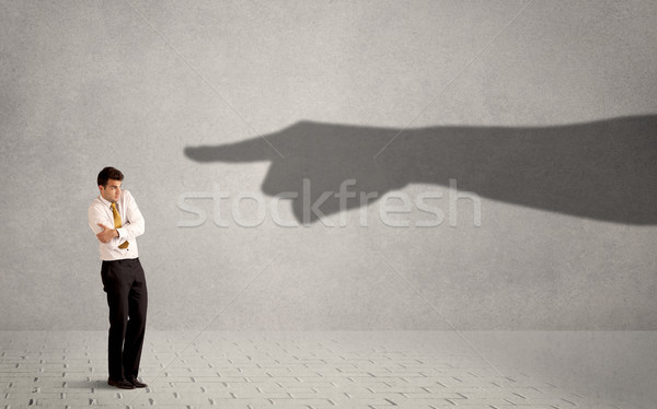 Business person looking at huge shadow hand pointing at him concept Stock photo © ra2studio