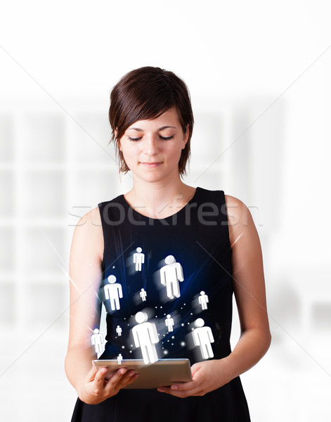Stock photo: Young woman looking at modern tablet with social icons