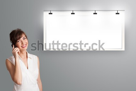beautiful young woman standing next to a modern copy space and making phone call Stock photo © ra2studio