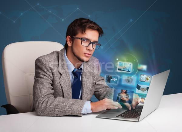 привлекательный молодым человеком сидят столе смотрят фото Сток-фото © ra2studio