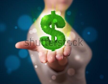 Fiatal nő bemutat zöld izzó dollárjel fiatal Stock fotó © ra2studio