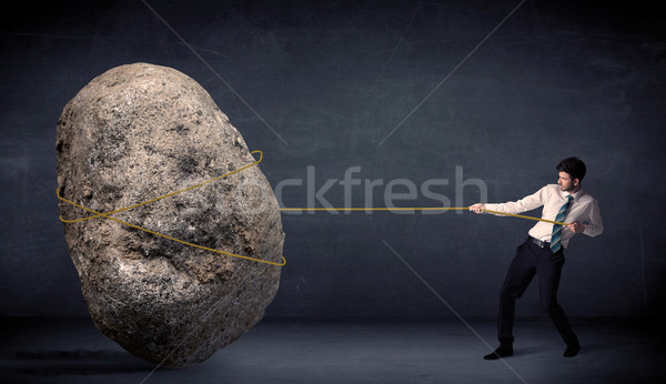 Stock photo: Businessman pulling huge rock with a rope