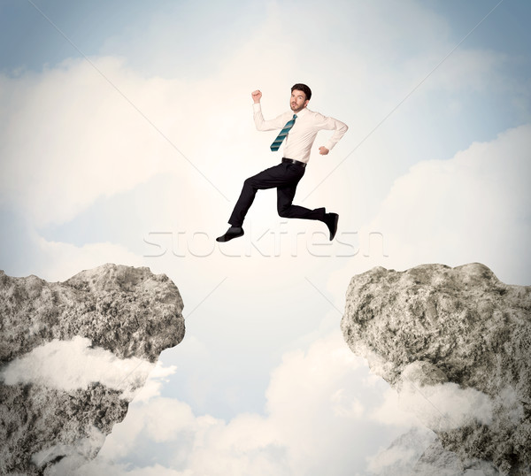 Happy business man jumping over a cliff  Stock photo © ra2studio