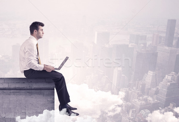 Sales person sitting on building edge in city Stock photo © ra2studio