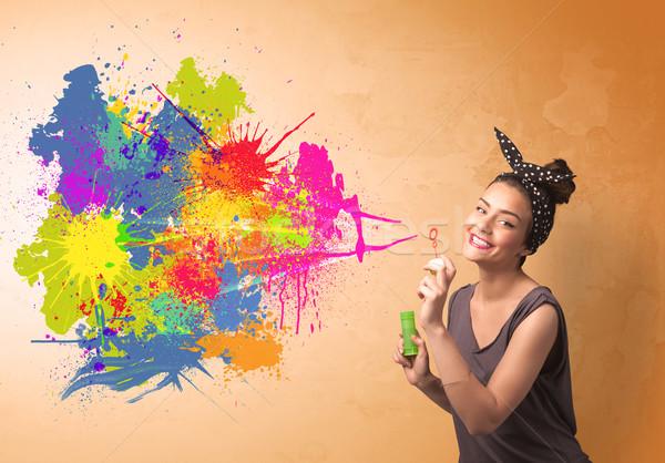 Cute girl blowing colorful splash graffiti  Stock photo © ra2studio