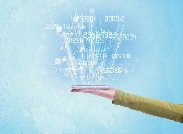 Hand holding phone with digital numbers Stock photo © ra2studio