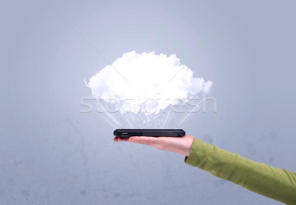 Hand holding phone with empty cloud Stock photo © ra2studio