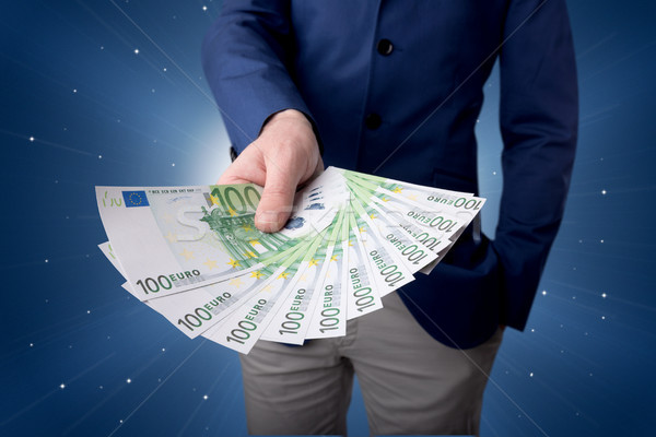 Businessman holding money Stock photo © ra2studio