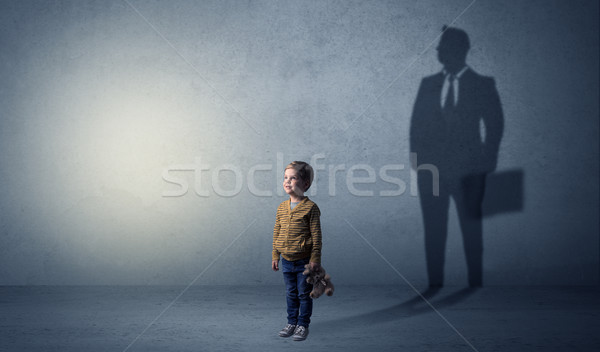 Little boy with businessman shadow Stock photo © ra2studio