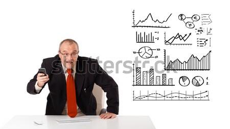 Foto d'archivio: Imprenditore · seduta · desk · diagrammi · grafici · isolato