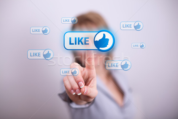 Woman pressing modern like button with one hand Stock photo © ra2studio