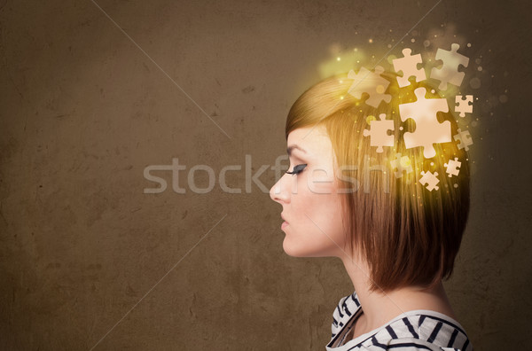 Young person thinking with glowing puzzle mind Stock photo © ra2studio