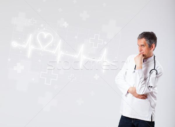 Doctor examinates heartbeat with abstract heart Stock photo © ra2studio