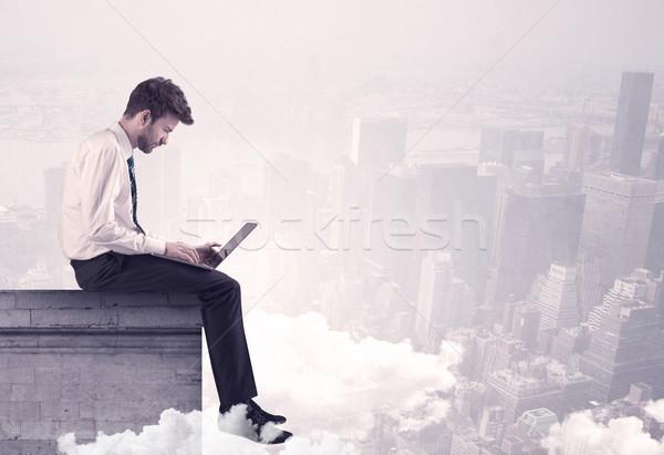 Sales person sitting on building edge in city Stock photo © ra2studio