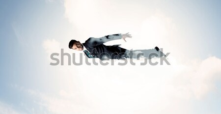 Business man flying like a superhero in clouds on the sky Stock photo © ra2studio