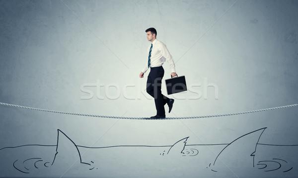 Businessman walking on rope above sharks Stock photo © ra2studio