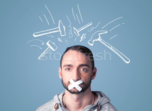 Young man with glued mouth and beating hammer marks Stock photo © ra2studio