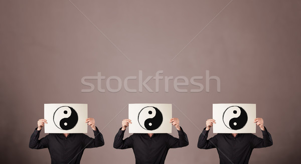 Handsome people in formal gesturing with yin yang sign on cardbo Stock photo © ra2studio