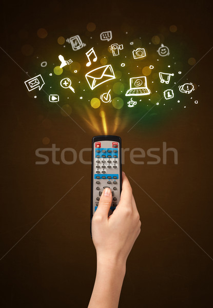 Stock photo: Hand with remote control and social media icons