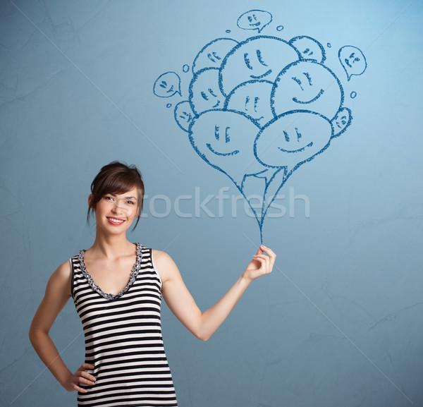 Happy woman holding smiling balloons drawing Stock photo © ra2studio