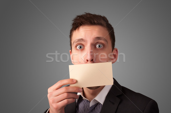 Businessman holding white card at front of her lips on gradient background Stock photo © ra2studio