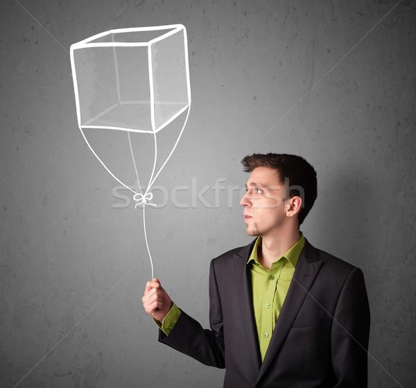 Businessman holding a cube balloon Stock photo © ra2studio