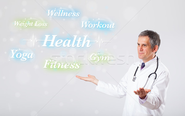 Clinical doctor pointing to health and fitness collection of wor Stock photo © ra2studio