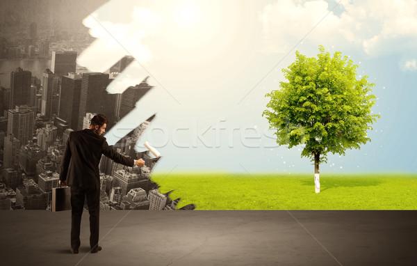 Salesman painting tree instead of city Stock photo © ra2studio