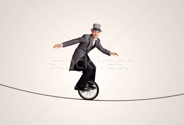 Extreme business man riding unicycle on a rope Stock photo © ra2studio