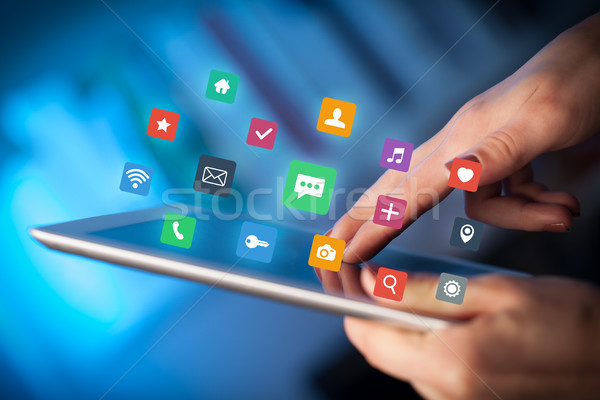 Fingers touching tablet with apps Stock photo © ra2studio