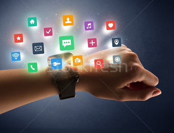 Female hand wearing smartwatch with app icons Stock photo © ra2studio