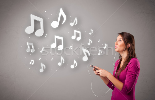 Pretty young woman singing and listening to music with musical notes Stock photo © ra2studio