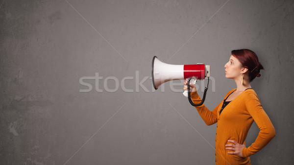 Girl shouting into megaphone on copy space background Stock photo © ra2studio