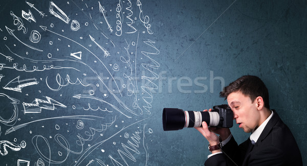 Photographer boy shooting images while energetic hand drawn lines and doodles come out of the camera Stock photo © ra2studio