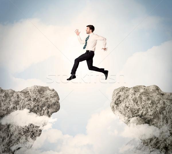 Feliz hombre de negocios saltar acantilado hombre montana Foto stock © ra2studio