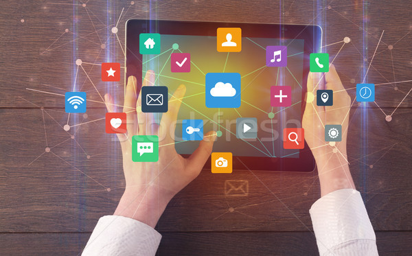 Stock photo: Hand using multitask tablet with application symbols and icons c