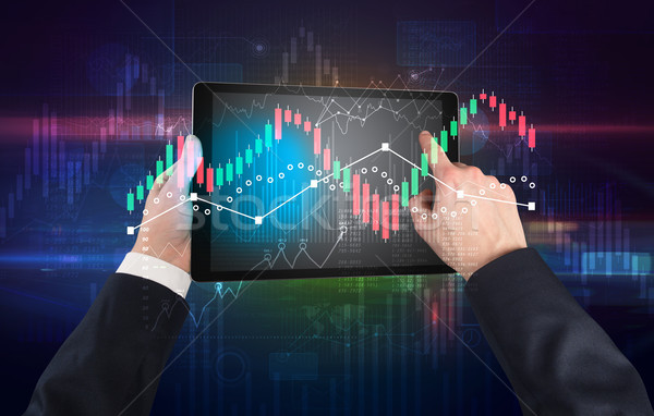 Hand holding tablet with global reports and stock market change concept Stock photo © ra2studio